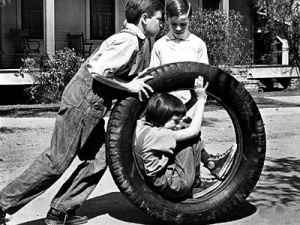 Jem and Dill hurling Scout into Boo Radley's yard in To Kill a Mockingbird