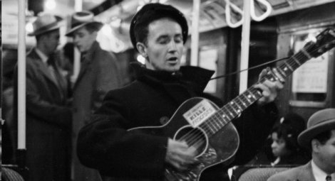 "Woody Guthrie. The sign on his guitar says, ""This machine kills fascists."" He was a tenant at Beach Haven, the Trump's first major housing project, in 1950."
